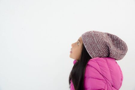 copyspace: Happy Asian girl wearing pink down jacket sitting on white wall with copyspace. Stock Photo