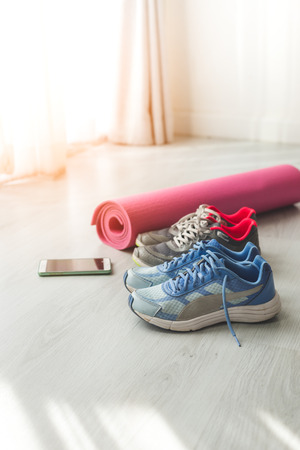 Dirty sport shoes on  floor with yoga mat and smartphone at home. Lifestyle concept.