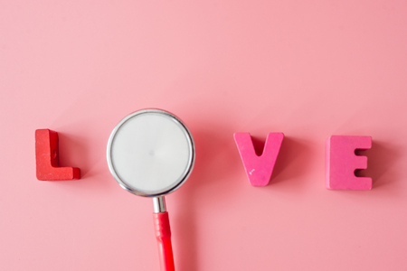 Stethoscope with love on pink background.