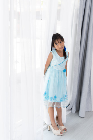 Cute Asian girl wearing her mother's high heel shoes standing near window at home.
