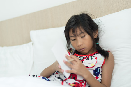 Asian girl writting something on paper.  Laying on bed.