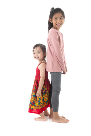 Asian girl and her sister standing together and looking at camera.  Happy children on white. Stock Photo