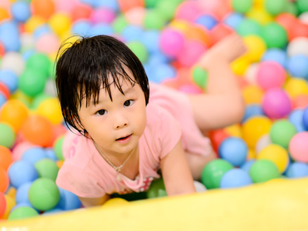 Happy Asian child with colorful plastic balls toy