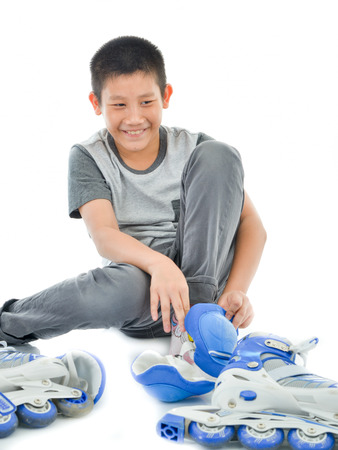 roller: Happy Asian boy wearing knee guard and shoes for playing roller blades on white.