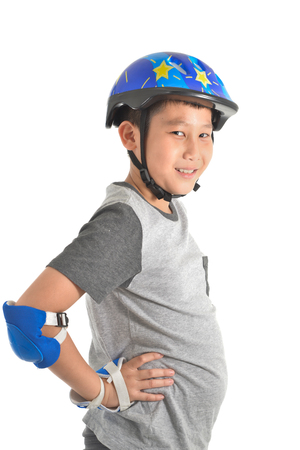 Happy Asian boy has a beer gut wearing safety guard for playing roller blades on white. Stock Photo