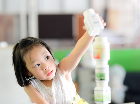 Asian girl playing block by plastic bottle at home, lifestyle concept photo