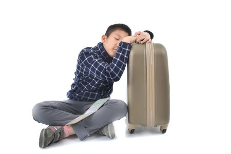 map case: Asian boy sleeping with suitcase and map isolated on white background.
