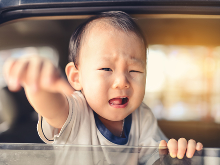 open windows: Crying Asian baby in car, safety concept. Stock Photo