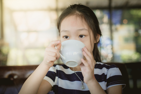 Asian girl drinking a cup of milk at home photo