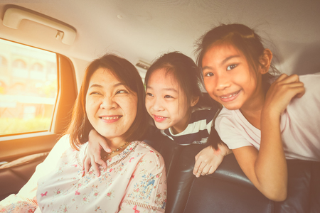 Happy kids and mother  travelling in car.