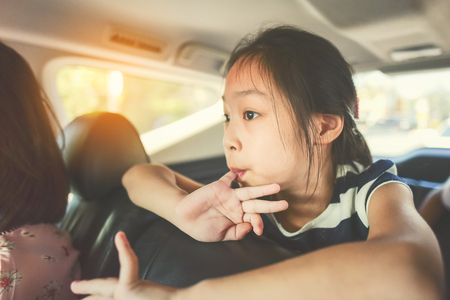 Asian girl sitting in car while travel with her family photo