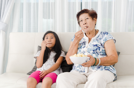 Asian senior woman eating popcorn with her grandchild while watching TV at home, selective focus photo