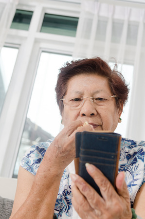 Asian senior woman eating popcorn while using smartphone at home. photo