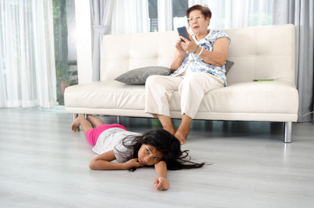 grandkids: Unhappy Asian girl lying down on wooden floor with her grandmother using smartphone on sofa background.  Lifestyle concept