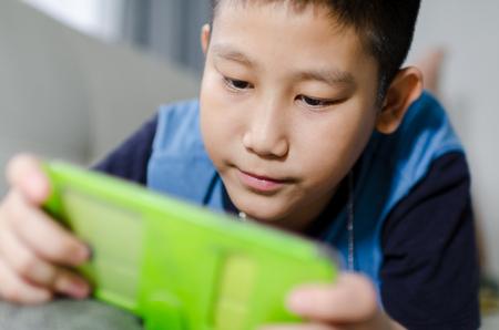 アジアの少年のソファの上に敷設し、スマート フォンでゲームをプレイ
