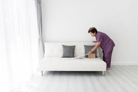 アジアのシニア女性の自宅のソファのクリーニング