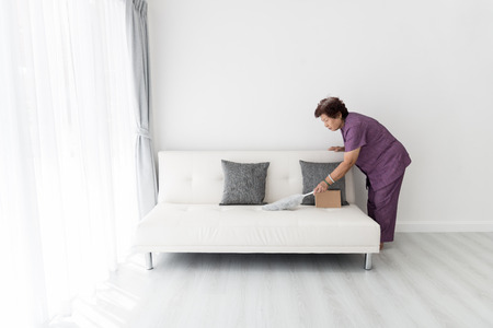 Asian senior woman cleaning couch at home