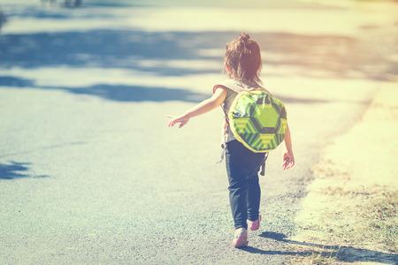 Backo of girl running on street outdoor