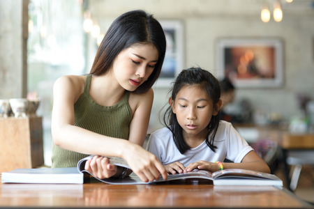 Beautyiful woman reading a book with her younger sister. 스톡 콘텐츠