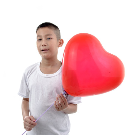 Asian boy holding red heart balloon on white background, love concept.