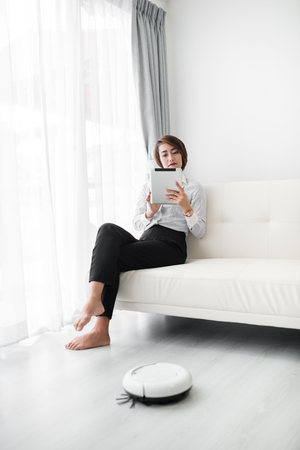 Smart businesswoman using smart phone and cleaning robot, lifestyle concept. Standard-Bild