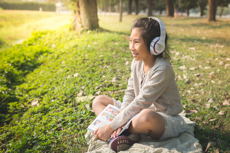 Happy girl sitting in the park and using headphone and holding cartoon book, lifestyle concept.
