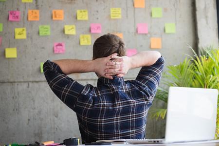 Tyłu przedsiębiorcy siedzącego w biurze i spójrz na kolorową lepką wiadomość na cementowej ścianie. Pojęcie stylu życia. Zdjęcie Seryjne