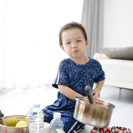 Cute Asian girl playing chef at home.