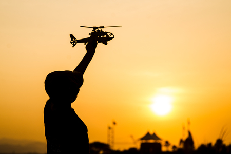 Silhouette boy playing  helicopter model with sun set.