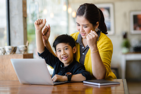 Happy Asian mother and her son raising their hands while win the online game together. Stockfoto