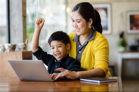 Happy Asian mother and her son raising their hands while win the online game together. Zdjęcie Seryjne