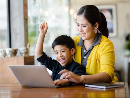 Szczęśliwa azjatycka matka i jej syn podnoszą ręce i wspólnie wygrają w grze online. Zdjęcie Seryjne
