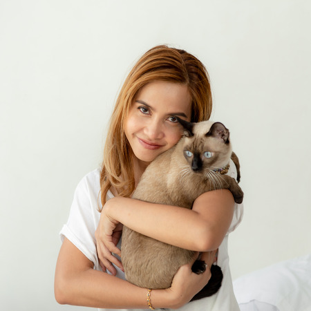 Happy Asian woman holding her cat on white background. Banque d'images