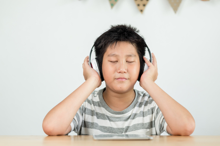 Happy preteen Asian boy using headphone and listening to music from tablet.