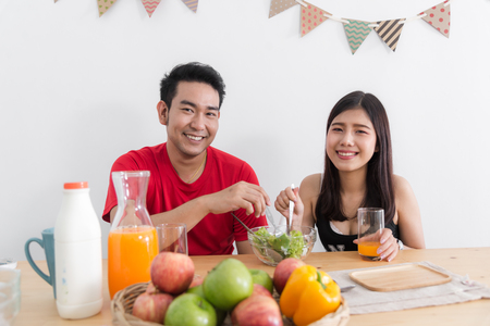 Asian couple feeding each other with salad, lover lifestyle concept. Stock Photo