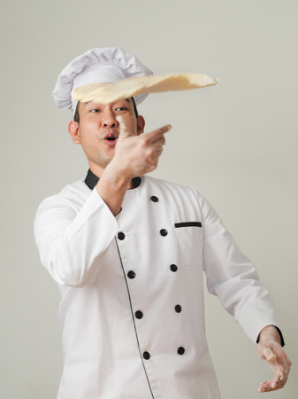 Motion blur, Pizza Chef makes the pizza dough spin in the air to make it thin and soft Stock Photo