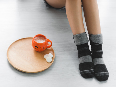 Woman legs wearing socks sitting on floor next to hot chocolate drink with marsmello, lifestyle concept.