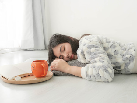 Sleeping Asian teenager girl wearing sweater on bed with orage cup beside her. 免版税图像