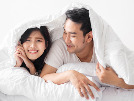 Happy Asian couple under white blanket together, lifestyle concept.