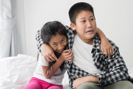 Happy Asian preteen boy hugging his younger sister at home.