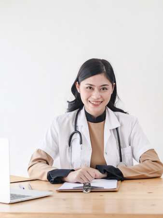 Female Asian doctor working at office desk and smiling at camera.