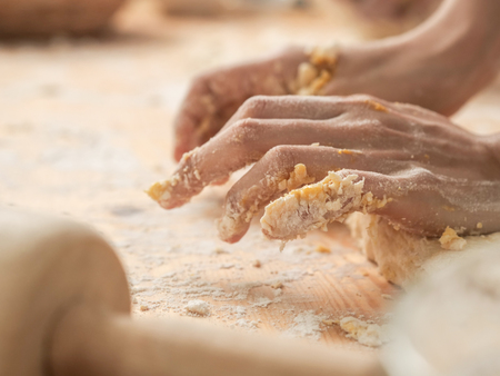 Motionblur chef hands preparing dough for pizza or bread on table closeup Stockfoto