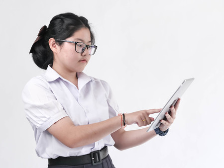 Asian student in uniform using tablet on white background. Banque d'images