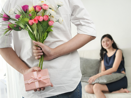 Man holding flowers bouquet and pink gift box for surprising his girlfriend, lifestyle concept.