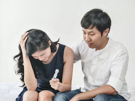 Worried couple checking pregnancy test sitting on a couch at home, lifestyle concept.