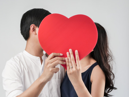 Happy couple in love holding red heart shape, valentine concept.