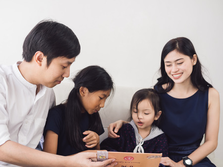 Happy Asian family reading a book together at home, lifestyle concept.
