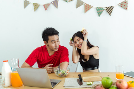 Happy Asian couple using laptop and eating salad and fresh fruit at home.