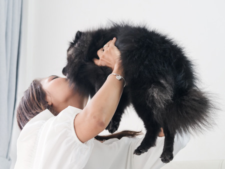 Happy Asian woman playing with her black dog on sofa at home, lifestyle concept Foto de archivo