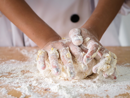 Kid hands in uniform preparing dough for pizza or bread, lifestyle concept.